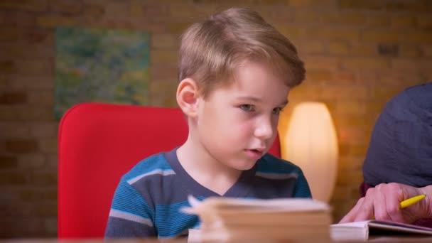 Blízký záběr malého chlapce, který se dívá do knihy studující se svou muslimskou matkou v hidžábu doma.