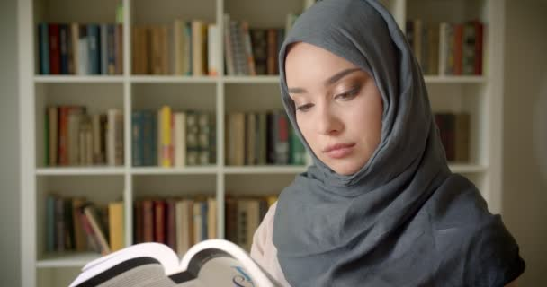 Profile portrait of muslim student in hijab reading book attentively smiles into camera at the library.