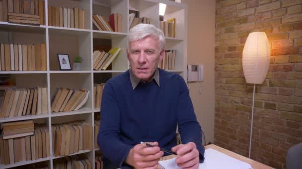 Interview eines älteren Mannes, der Fragen in die Kamera stellt, interessiert und begeistert auf Bücherregalen steht.