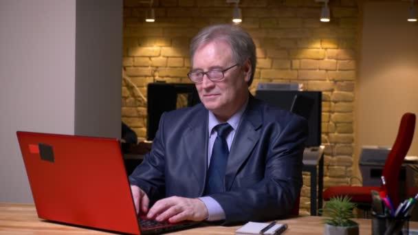 Porträt des Seniors in formellen Kostüm Tippen auf Laptop freudig und positiv im Amt.