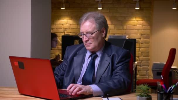 Porträt von Senior Mann in Brille in formellen Kostüm arbeiten mit Laptop aufmerksam im Büro.
