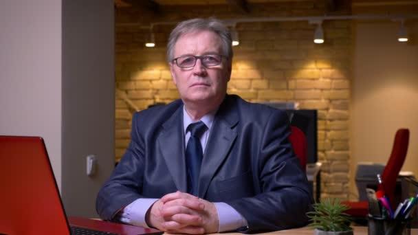 Porträt eines älteren Mannes in festlichem Kostüm, der vor dem Laptop sitzt und im Büro ernsthaft in die Kamera schaut.