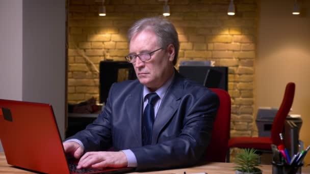 Portrét vyššího podnikatele v formálních kostýmech psaní na přenosném počítači je pozorný a usměvatelný na kameru a úsměvy v kanceláři.