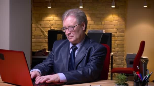 Portrét vyššího obchodníka v oficiálním kostýmu psaní na přenosném počítači se obrací na kameru a usměje se v kanceláři.