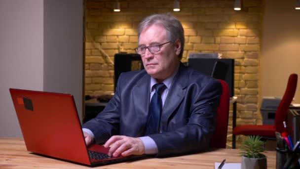 Portrait of senior man in glasses and formal costume working with laptop being annoyed and irritated in office.