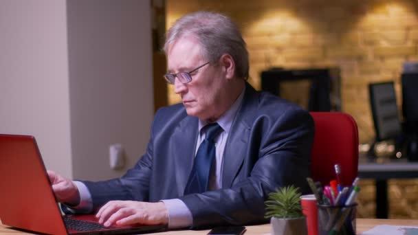 Porträt eines leitenden Geschäftsmannes in formellen Kostümarbeiten mit Laptop und Smartphone gleichzeitig im Büro.