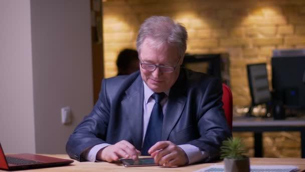 Senior Geschäftsmann in formellen Kostüm sitzen vor Laptop-Uhren in Tablet ist fröhlich im Büro.