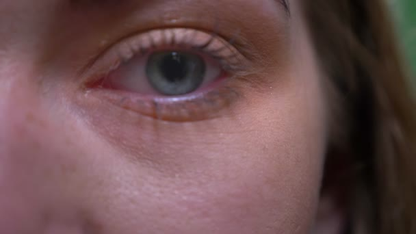 Zavřít jeden oční portrét blonďaté mody, klidně a pozorně sledovat fotoaparát na zeleném pozadí.