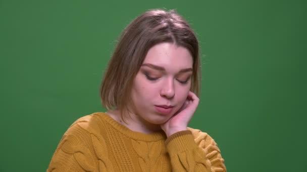 Closeup lő fiatal vonzó, rövid hajú nő, hogy félénk nézett kamera háttérrel izolált zöld