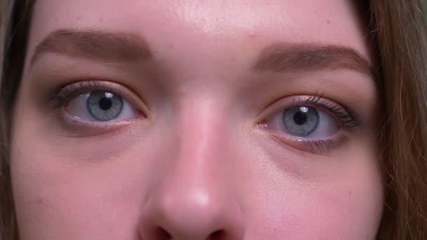 Closeup lő fiatal vonzó, rövid hajú női arc nézi kamera háttérrel izolált zöld