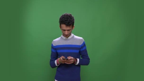 Nahaufnahme Shooting von jungen attraktiven indischen Mann mit dem Telefon mit Hintergrund isoliert auf grün