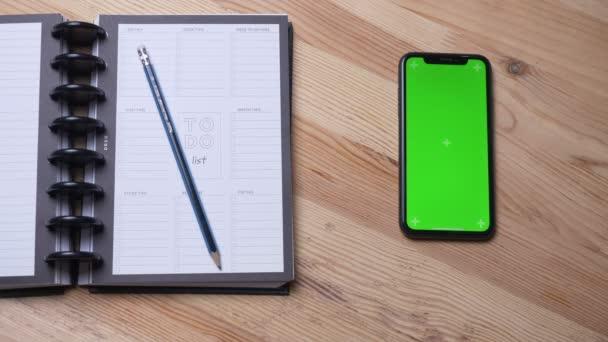 Horní stříšku samičí ruky s telefonem se zelenou obrazovkou, která se nachází na stole vedle deníku kultu v kanceláři
