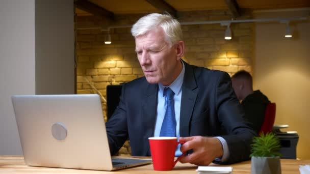 Closeup shoot of old caucasian businessman using the laptop and drinking coffee being busy and focused indoors in the office on the workplace
