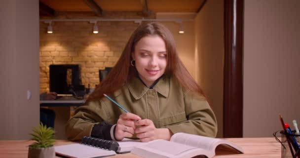Portré fiatal női hallgató előtt könyv csinál vele házi órákat a kamera hivatalban.