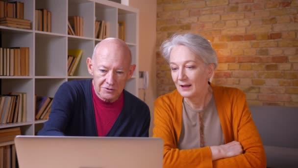 Seniorenkaukasisches Paar schaut freudig in Laptop zu Hause.
