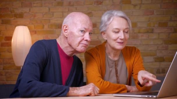 Kettő haladó idősebb szürke-hajú kaukázusi házastársak néz-ba laptop és vita ez hivatalban.