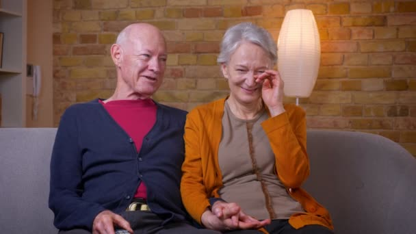 Senior kaukázusi házastársak nézni komédia TV nevetve könnyek a kanapén nappaliban.