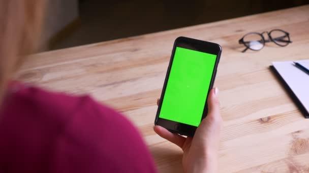 Zadní střela pro ženu, která drží svisle smartphone se zelenou chromou obrazovkou v kanceláři.