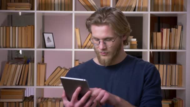 Closeup Střílejte dospělého studenta, který používá tablet, a zobrazuje zelenou obrazovku v univerzitní knihovně uvnitř