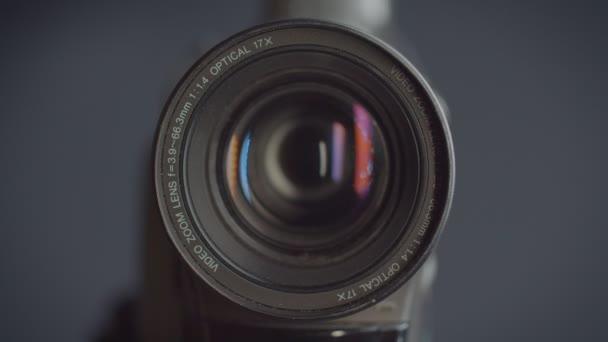 Nahaufnahme des Objektivs einer Videokamera mit roten Reflexen auf der Linse.