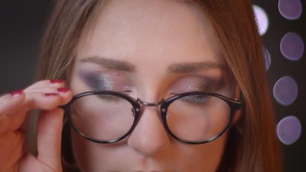 Closeup portrét mladé bělošské dívky v brýlích, které se dívají na kameru a usmívají se na pozadí