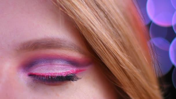 Nahaufnahme halbes Gesicht Shooting der jungen attraktiven kaukasischen Frau mit rosa schönen rosa Glitzer Make-up Blick in die Kamera mit Bokeh Hintergrund