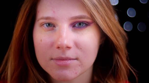 Closeup lő a fiatal, vonzó kaukázusi nő feltárása félig alkalmazott smink keres egyenesen a kamera