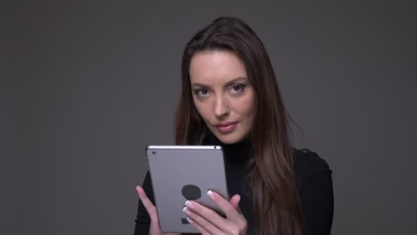 Portrait of attractive brunette woman holding tablet smiling into camera positively isolated on gray background.