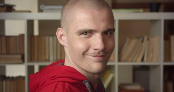 Closeup portrét mladého atraktivního bělošského studenta, jak se dívá na kameru a usmívá se v univerzitní knihovně uvnitř