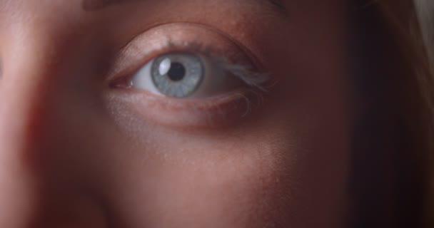 Vértes fél arca portré fiatal csinos kaukázusi nő, kék szemmel keres egyenesen a kamera