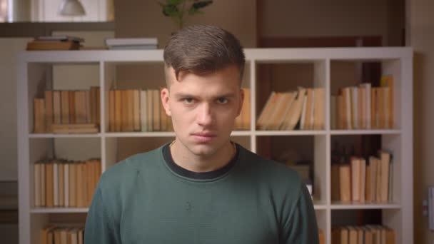 Portré fiatal férfi diák figyeli súlyosan kamera álló könyvtár.