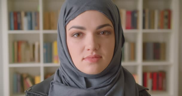 Closeup portrait of young attractive muslim female student in hijab looking at camera in the college library indoors