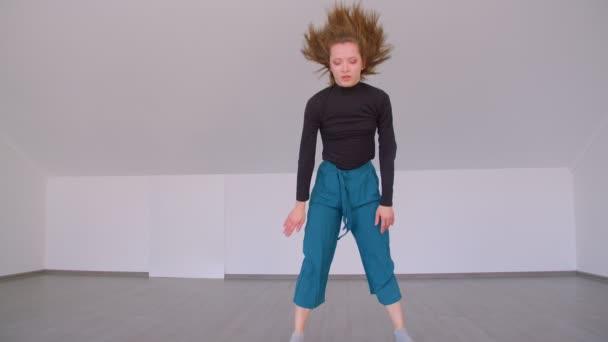 Pohyb mladé krásné kvalifikované ženy, která provádí emocionální tanec v místnosti uvnitř bytu