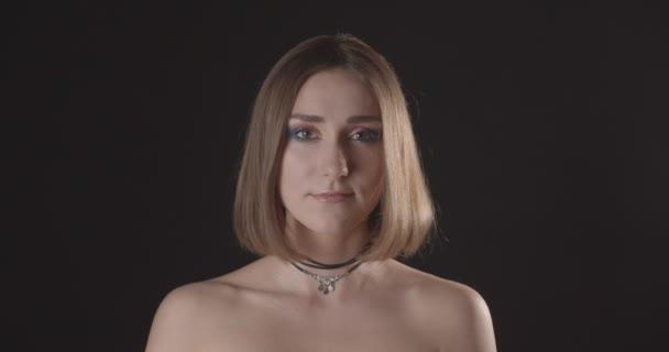 Closeup lő fiatal csinos kaukázusi rövid hajú nő aranyos smink nézett kamera háttérrel izolált fekete