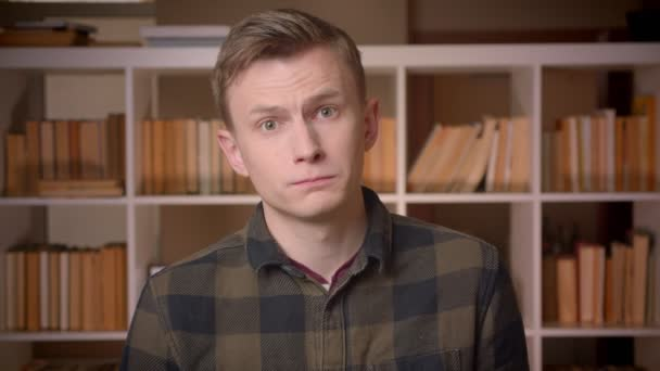 Closeup shoot of young attractive caucasian male student nodding saying yes looking at camera in the college library