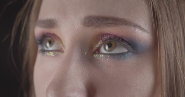Closeup portrét mladé kavkazské, krátkě prošedivělý ženský obličej s očima s třpytem, který pózoval před kamerou a pozadí je izolován na černém