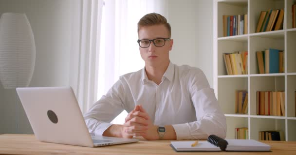 Closeup portrait of young handsome caucasian businessman in glasses using the laptop looking at camera smiling cheerfully indoors in the office