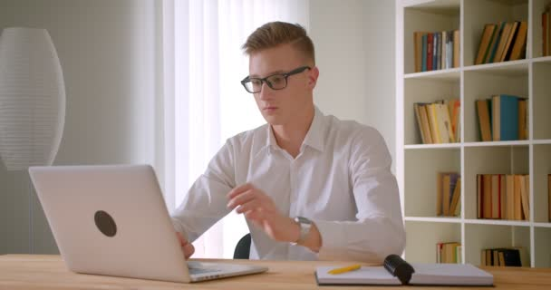 Closeup portrait of young handsome caucasian businessman in glasses using the laptop and taking notes indoors in the office