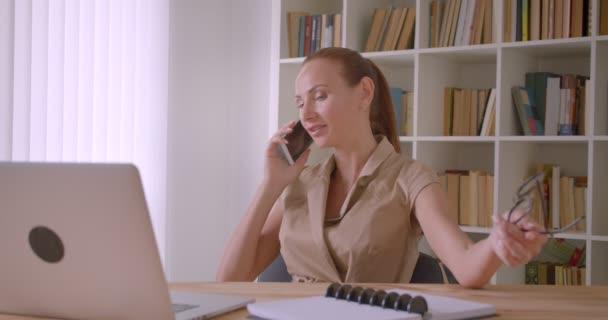 Veselá běločská žena, která mluví o mobilu v kanceláři, se pobavila a šokovala.
