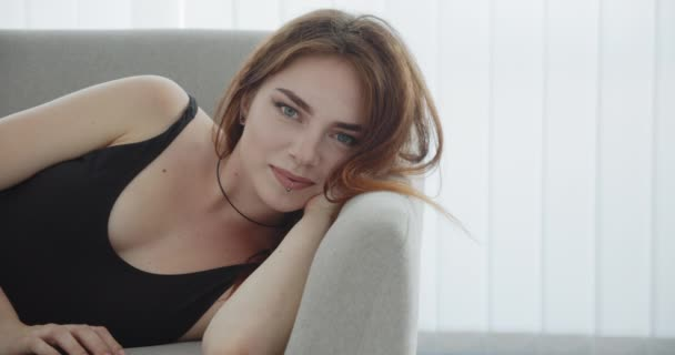 Closeup shoot of young seductive caucasian female in black bodysuit laying on the couch looking at camera and smiling happily indoors