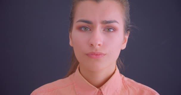 Closeup portrét mladé bělošské ženské, která se dívá na kameru s pozadím izolovaným na šedém
