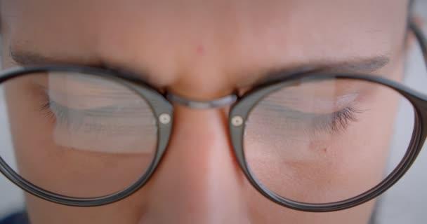 Progresivní Kavkazan v brýlích s ponyocasou prací s elektronickým zařízením pozorující pohled na kameru.