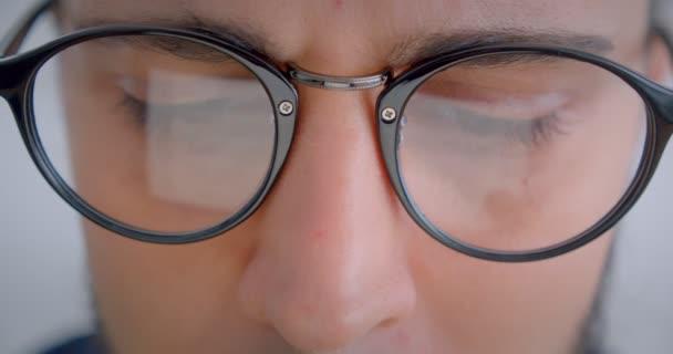 Progresivní Kavkazan v brýlích s vířovou prací s elektronickým zařízením, který je pozorný.