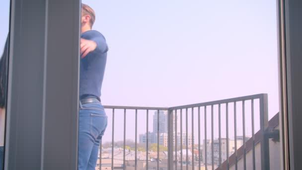 Fiatal kaukázusi pár szerelmes felöleli az erkélyen, és élvezi csodálatos város kilátás.