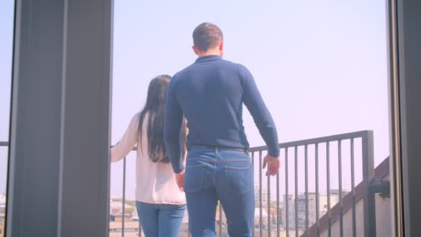 Rear portrait of young caucasian couple in love embraces on balcony and enjoying magnificent city view.