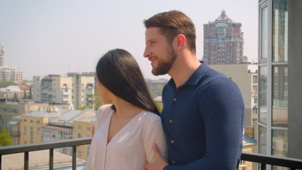 Young caucasian couple in love hugging and kissing tenderly on terrace enjoying city view.