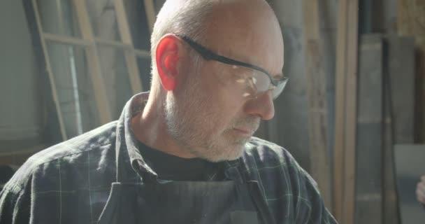 Nahaufnahme Porträt eines leitenden Tischlers mit Schutzbrille, der den Prozess in der Holzfabrik kontrolliert, schaut gelassen in die Kamera.