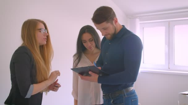Young caucasian couple signs documents and gets keys from their new flat from real-estate agent being excited.