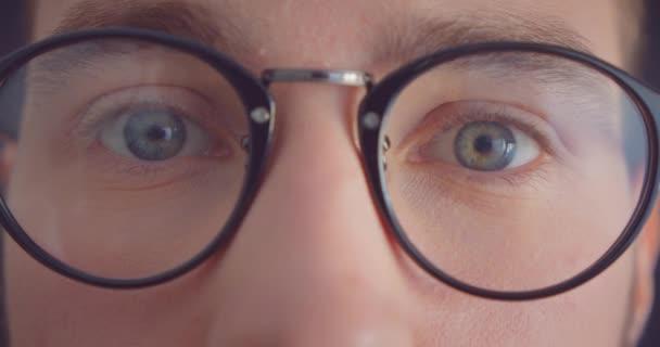 Closeup portrét mužské tváře v brýlích na kameře s usměvavou výrazem