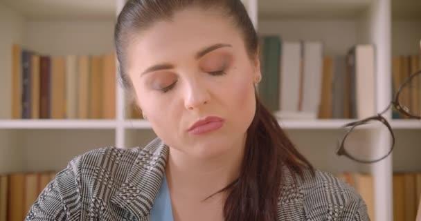 Střelili zastřelena mladé kavkazské ženy a dívala se na kameru v knihovní kanceláři s policemi na pozadí
